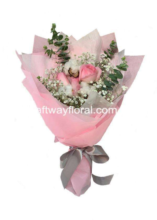 This bloom consists of pink roses, dried cotton flowers, white baby's breaths, and eucalyptus.