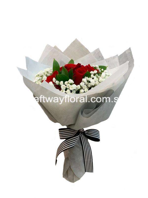 This bloom consists of red roses, white baby's breaths, and ruscus wrapped in white and grey wrapping.