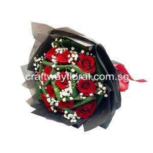 This blooms contain red roses, white baby's breaths and foliage wrapped in black wrapping.