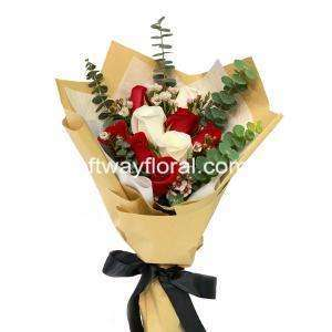 This bloom consists of red roses, white roses, wax flowers, and eucalyptus wrapped in white and kraft wrapping.