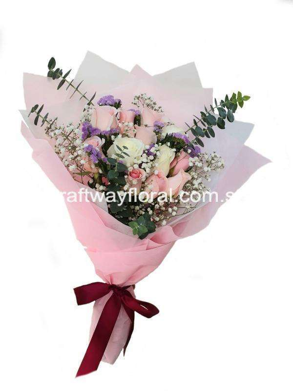 This bloom consists of pink roses, white roses, light purple statices, white baby' breaths, and eucalyptus.