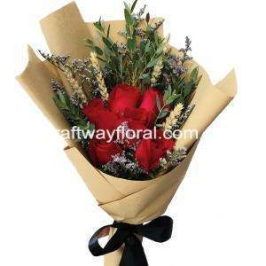 This bloom consists of red roses, dried wheat, purple caspias, and eucalyptus wrapped in brown kraft paper.