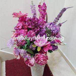 Mixtures of wild-looking purple artificial flowers arranged in a white ceramic vase.