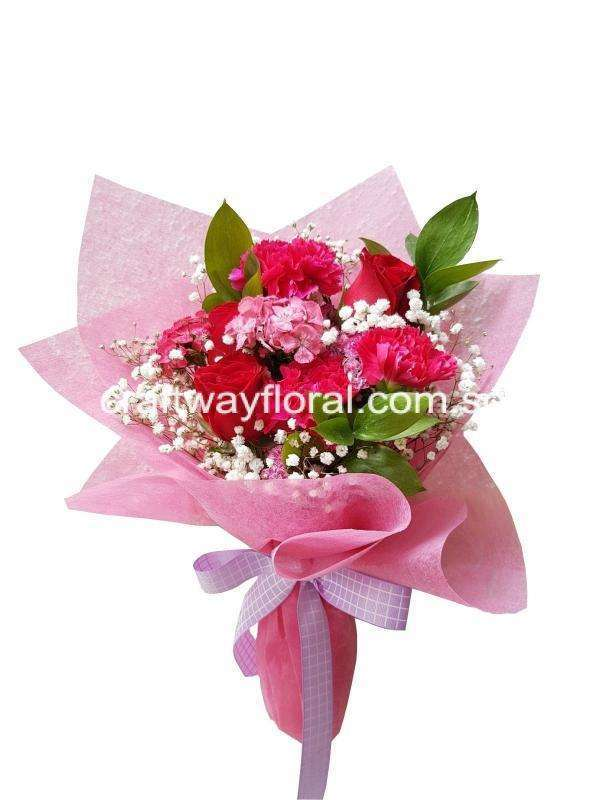 Blooms consists of mixtures of roses, carnations foilages and fillers wrapped in pink .