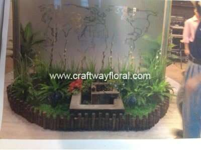 Artificial Plants decorated together with an indoor miniature fountain.