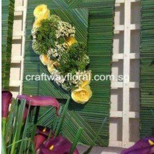 Green Wall Decor with artificial yellow flowers and straws.