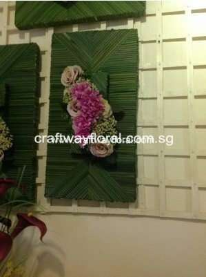 Green Wall Decor decorated with mixtures of pink artificial flowers and straws.