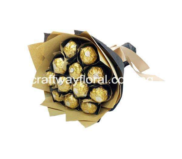 Edible Rocher Choclates wrapped in black and kraft wrapping.