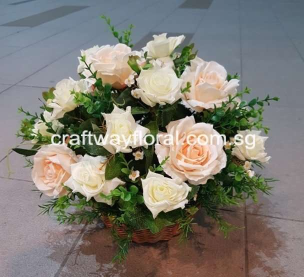 Artificial Champagne and white roses arranged neatly in a round centrepiece basket