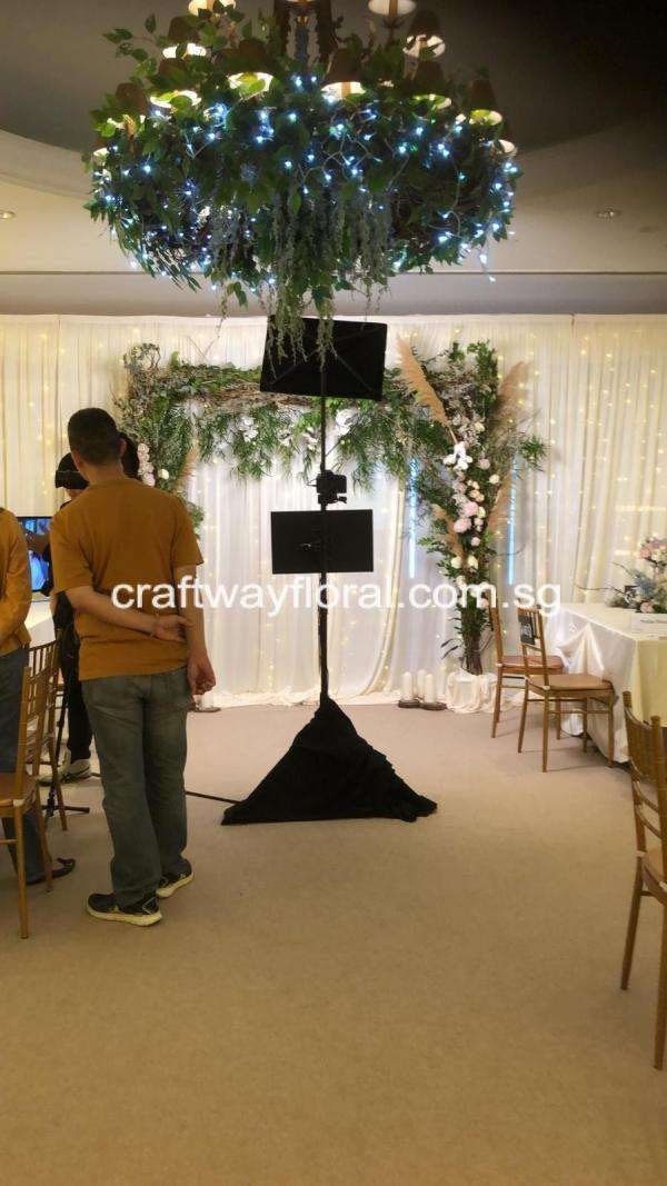 Floral wedding arch backdrop for wedding photo-takings as well as ceiling lamp decorated with foilages to give a magnificent wedding vibe.