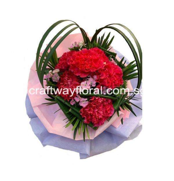 This bloom contains shocking pink carnations, sweet williams, and other foliages.